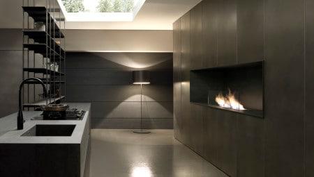 Veduta del piano cucina Blade di Modulnova e parete con caminetto in gres pietra Savoia antracite.