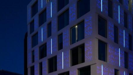 Il nuovo edificio Motel One progettato da Mackay + Partners nello storico quartiere Minories della City di Londra presenta una facciata illuminata realizzata con la superficie hi-tech DuPont™ Corian® - foto courtesy Mackay + Partners