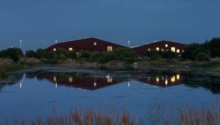 Una suggestiva immagine notturna del 'Soil Centre Copenhagen'' della società danese By&Havn: all'edificio fa capo la bonifica della terra proveniente dai cantieri edili attivi sul territorio circostante. L'edificio si affaccia su un'area verde, oasi naturale protetta.