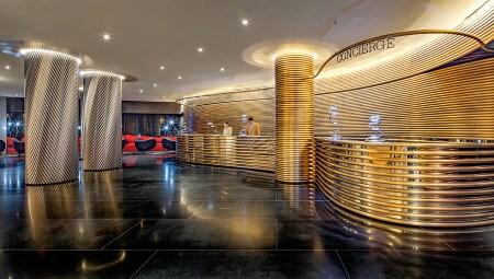 Scorcio della zona lobby. Il tubolare d'ottone che riveste colonne e reception desk è stato fornito  e messo in opera su disegno di Ron Arad Architects dall'italiana Realize.