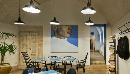 La sala con i tavoli al centro dai piani in pietra lavica smaltata blu a mano e le sedute all black di GTV (Gustav), Vitra (Eames Plastic Side Chair) che spiccano per contrasto nell'involucro chiaro in pietra locale. Appesa alla parete, un'opera di Sergio Fiorentino.