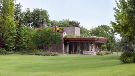La casa vive in perfetta simbiosi con la natura, diventando un tutt'uno con il paesaggio, grazie anche al giardino pensile.