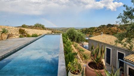 Dalla quota della piscina si gode di una straordinaria vista sull'assolata campagna siciliana con il mare sullo sfondo. Si notano gli spessi  muri di contenimento in pietra a secco costruiti a chilometro zero.