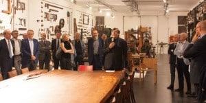 """Maurizio Riva con alcuni suoi ospiti all'interno del Museo del legno. In primo piano il tavolo """"Antico"""" in legno millenario di Kauri datato 48.000 anni e lungo 12 metri con base in ferro, disegnato dall'architetto Renzo Piano"""