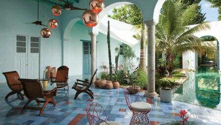Aperto sulla piscina, il patio funge come generoso spazio di decompressione.  Eterogenei gli arredi:  lampade a sospensione in rame di Tom Dixon e sedute Re-Trouvé di Patricia Urquiola per Emu.