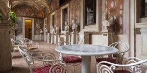 """Sedie in ferro battuto con cuscini """"Arance"""" e tavolo """"Corona di fiori"""" di Fornasetti nella Loggia dipinta del Museo Nazionale Romano-Palazzo Altemps ©Electa ph S. Castellani"""