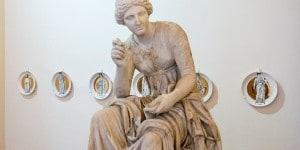 """Statua di Calliope. Set di piatti """"Le muse"""" di Fornasetti. Museo Nazionale Romano-Palazzo Altemps ©Electa ph S. Castellani"""