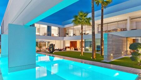 Vista della corte-giardino dalla piscina. Tutti gli ambienti si aprono con vetrate continue verso lo spazio centrale, reinterpretando in chiave contemporanea la tipologia a corte della casa araba tradizionale.