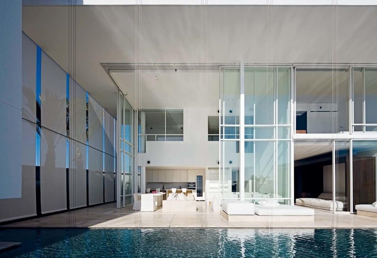Il fronte vetrato di una villa a doppio livello aperta verso lo specchio d'acqua connettivo e proiettata verso l'orizzonte del mare. Le grandi vetrate a tutt'altezza sono schermabili da tende avvolgibili esterne