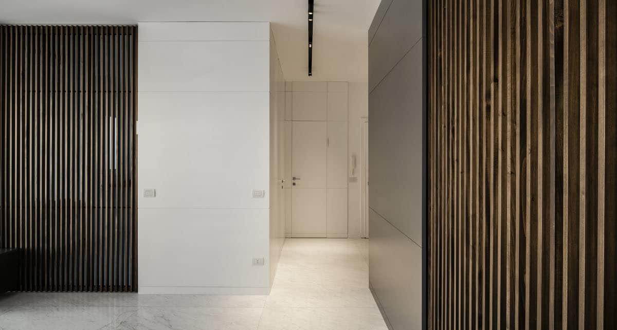 _Un pregiato pavimento in marmo di Carrara bianco opaco e un sistema di boiserie in legno laccato bianco e antracite caratterizzano lo spazio
